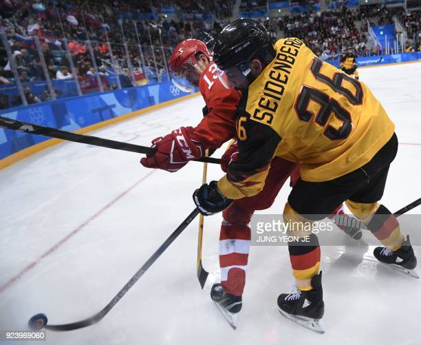 Russia's Pavel Datsyuk and Germany's Yannic Seidenberg vie for the puck in the men's gold medal ice hockey match between the Olympic Athletes from...
