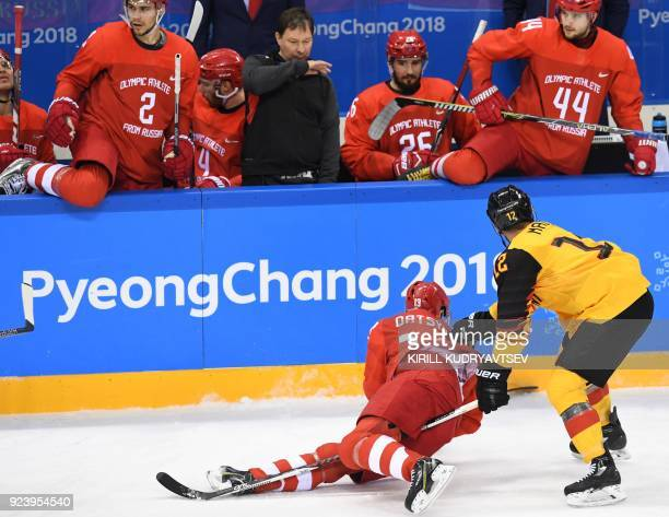 Russia's Pavel Datsyuk trips over Germany's Brooks Macek in the men's gold medal ice hockey match between the Olympic Athletes from Russia and...