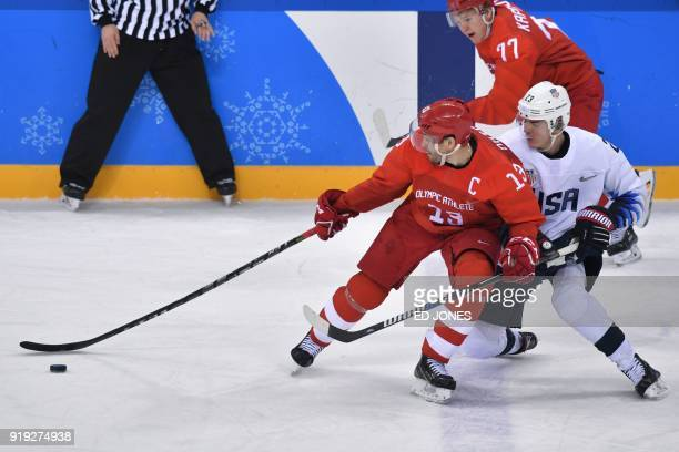 Russia's Pavel Datsyuk US Troy Terry and Russia's Kirill Kaprizov vie for the puck in the men's ice hockey preliminary round group B game between the...