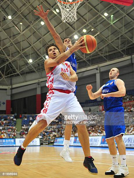 Russia's Pavel Sergeev makes a backward pass under pressure from Serbia's Marko Keselj during their Stankovic Cup basketball game in Hangzhou on July...