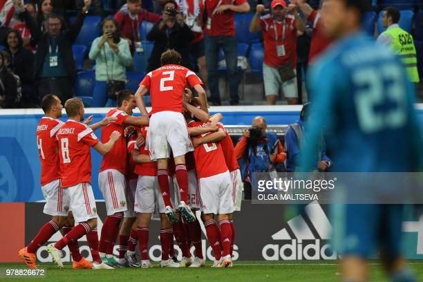 Russia's players celebrate after Egypt's defender Ahmed Fathi own goal during the Russia 2018 World Cup Group A football match between Russia and...