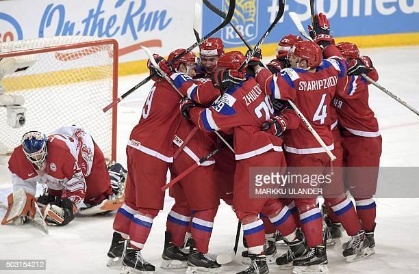 Russia's players celebrate their team's winning goal behind Denmark's goalie Thomas Lillie during the 2016 IIHF World Junior Ice Hockey Championship...