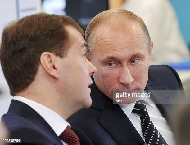 Russia's President Dmitry Medvedev and Prime Minister Vladimir Putin speak while visiting the United Russia ruling party headquarters in Moscow on...