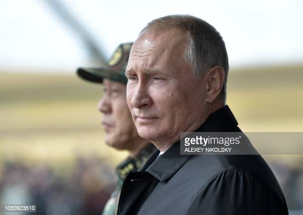 Russia's President Vladimir Putin and China's Defense Minister Wei Fenghe watch the parade of the participants of the Vostok2018 military drills at...