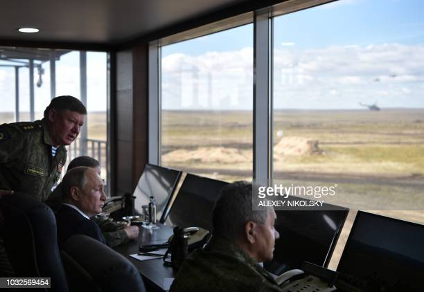 Russia's President Vladimir Putin and Defence Minister Sergei Shoigu watch the Vostok2018 military drills at Tsugol training ground not far from the...