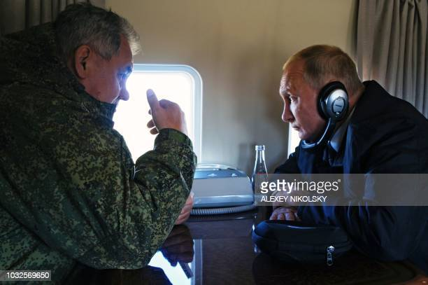 Russia's President Vladimir Putin and Defence Minister Sergei Shoigu fly over Tsugol training ground as they arrive to watch the Vostok2018 military...
