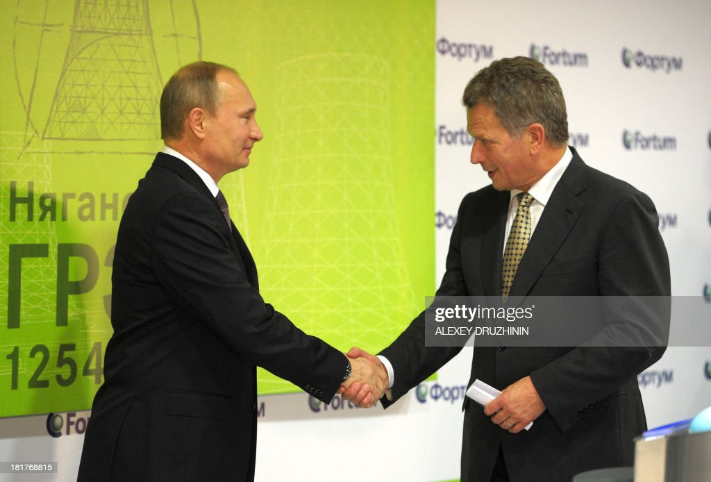 Russia's President Vladimir Putin (L) and his Finnish counterpart Sauli Niinisto (R) shake hands as they take part in ceremony to launch a Fortum Corporation's power plant in Nyagan, in western Siberia, on September 24, 2013.