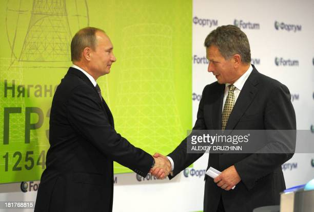 Russia's President Vladimir Putin and his Finnish counterpart Sauli Niinisto shake hands as they take part in ceremony to launch a Fortum...