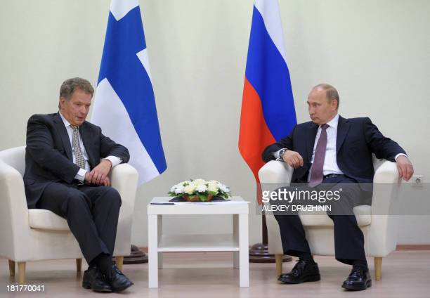 Russia's President Vladimir Putin and his Finnish counterpart Sauli Niinisto speak during their meeting in Nyagan in western Siberia on September 24...