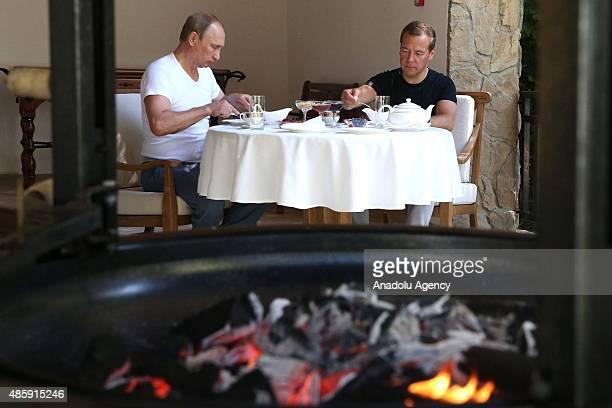 Russia's President Vladimir Putin and Prime Minister Dmitry Medvedev have breakfast at Bocharov Ruchei residence in Sochi, Russia on August 30,2015.