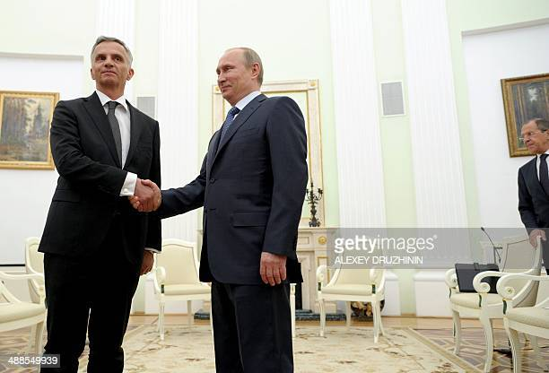 Russia's President Vladimir Putin and the head of the Organisation for Security and Cooperation in Europe Swiss President Didier Burkhalter shake...
