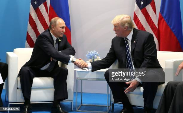 Russia's President Vladimir Putin and US President Donald Trump shake hands during a bilateral meeting on the sidelines of the G20 summit in Hamburg...