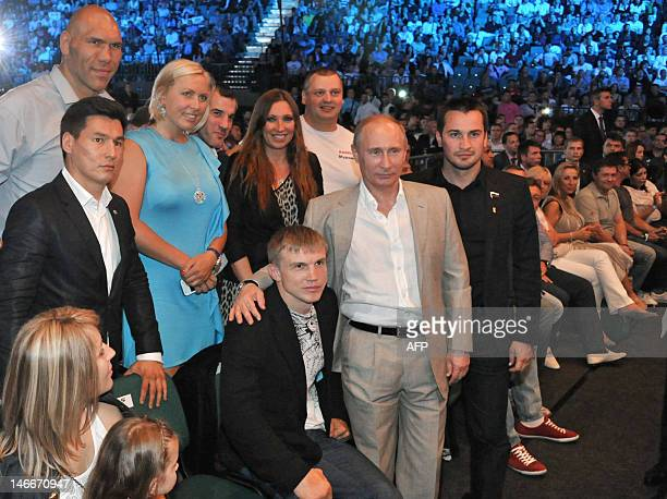 Russia's President Vladimir Putin applauds after watching a mixed martial arts fight at Ice Palace in Saint-Petersburg, late on June 21 with former...