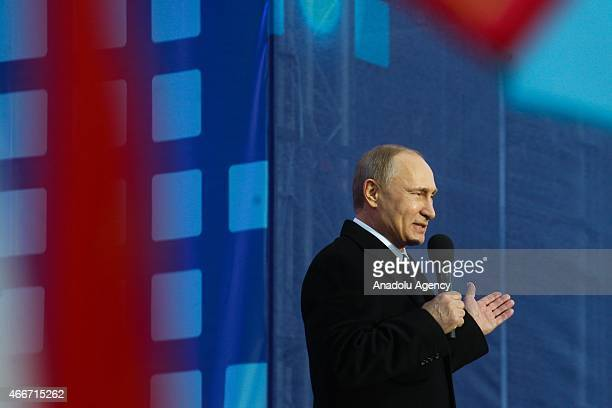 Russia's President Vladimir Putin attends a rally and a concert by the Kremlin Wall in central Moscow on March 18 marking the one year anniversary of...