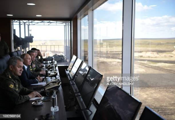 Russia's President Vladimir Putin Defence Minister Sergei Shoigu and Chief of the General Staff of the Russian Armed Forces Valery Gerasimov watch...