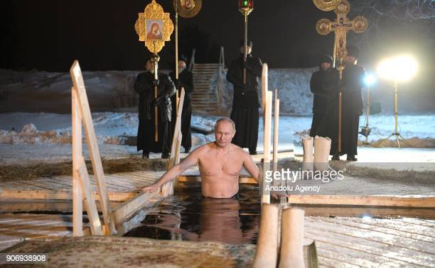 Russia's President Vladimir Putin dips in the icy waters of Lake Seliger during the celebration of Epiphany in Tver Region Russia on January 19 2018...