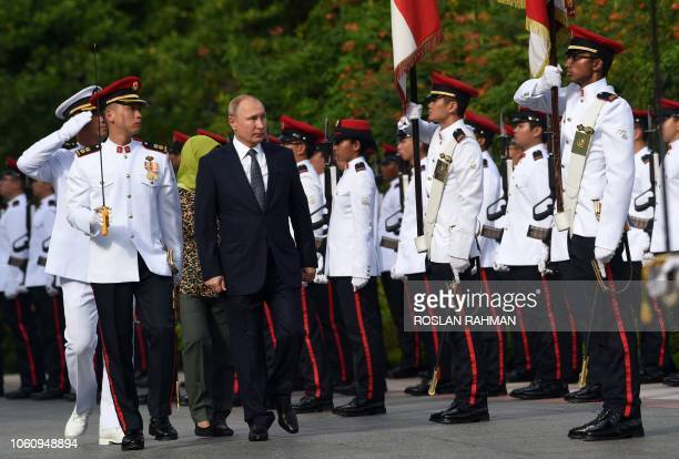 TOPSHOT Russias President Vladimir Putin followed by Singapores President Halimah Yacob inspect a guard of honour during a welcoming ceremony at the...