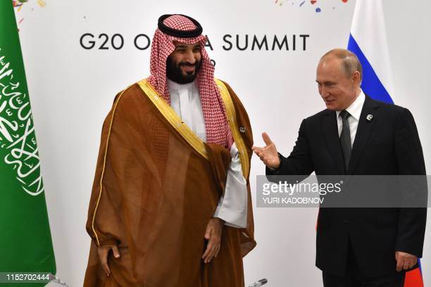 Russia's President Vladimir Putin gestures toward Saudi Arabia's Crown Prince Mohammed bin Salman during a meeting on the sidelines of the G20 Summit...