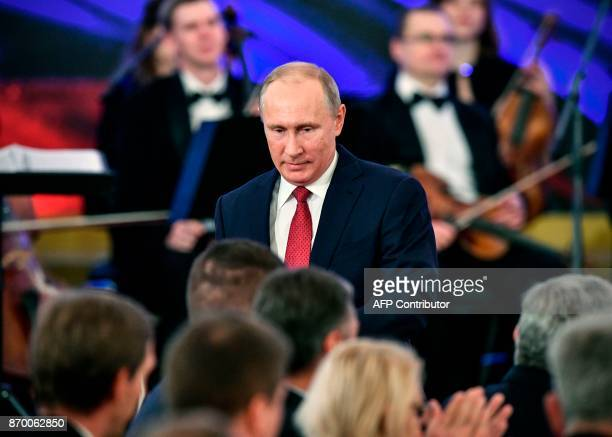 Russia's President Vladimir Putin is greeted by attendees during a reception in Moscow on November 4 as a part of celebrations marking Russian...