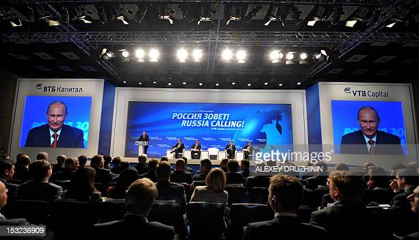 Russia's President Vladimir Putin is seen on the huge screens as he addresses an investment conference hosted by VTB Capital in Moscow on October 2...