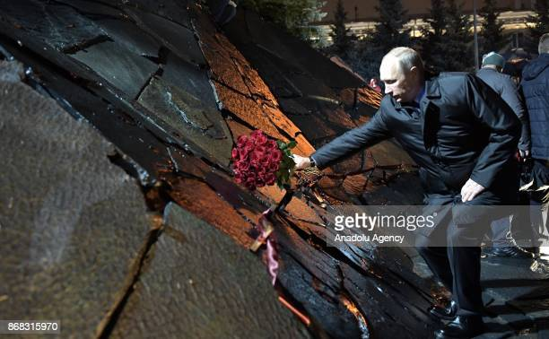 Russia's President Vladimir Putin lays a bunch of red roses at the unveiling of the Wall of Grief memorial for the political repression victims by...