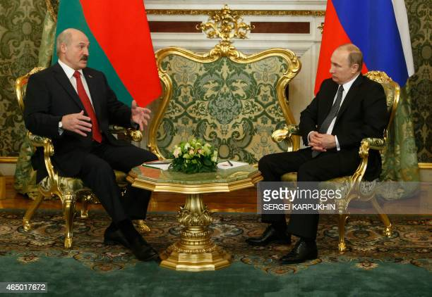 Russia's President Vladimir Putin listens to his Belarus' counterpart Alexander Lukashenko during their meeting part of a session of the Supreme...