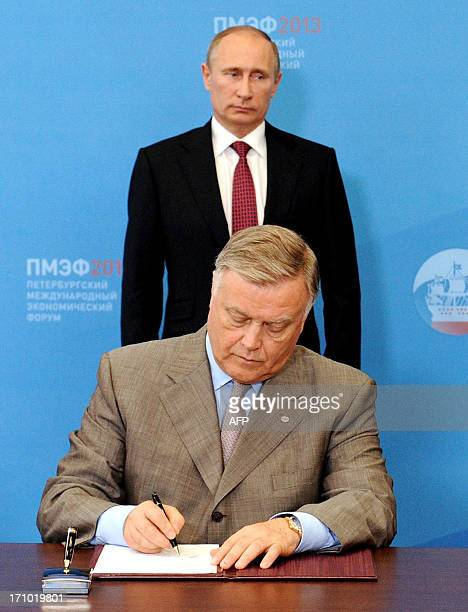 Russia's President Vladimir Putin looks on as he and Russian Railways head Vladimir Yakunin take parts in a signing ceremony suring in the economic...