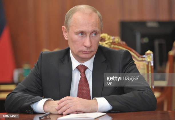 Russia's President Vladimir Putin looks on during a meeting at the Kremlin in Moscow on December 28 2012 Putin signed today into law a ban on the...