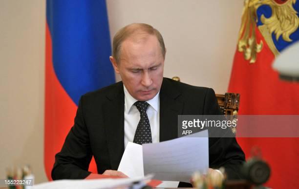 Russia's President Vladimir Putin looks through documents at his study in Putin's NovoOgaryovo residence outside Moscow on November 2 2012 Putin is...