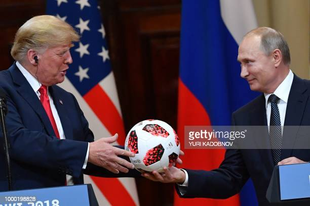 TOPSHOT Russia's President Vladimir Putin offers a ball of the 2018 football World Cup to US President Donald Trump during a joint press conference...