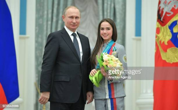 Russia's President Vladimir Putin presents Olympic champion figure skater Alina Zagitova with an Order of Friendship at a ceremony to award Russian...