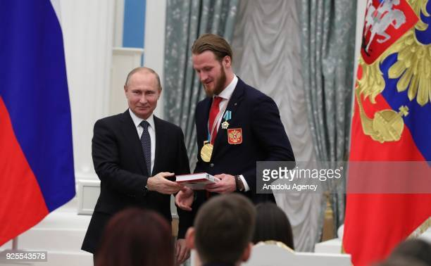 Russia's President Vladimir Putin presents Olympic champion ice hockey player Ivan Telegin with an Order of Friendship at a ceremony to award Russian...