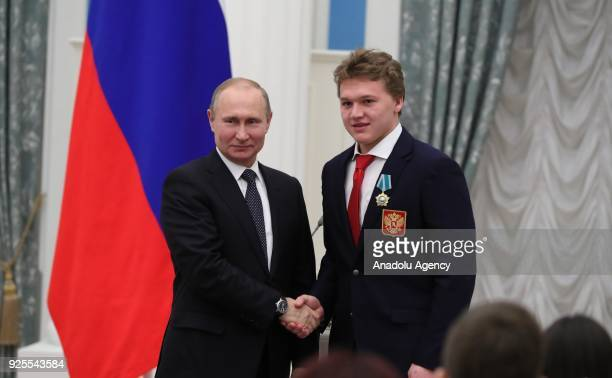 Russia's President Vladimir Putin presents Olympic champion ice hockey player Kirill Kaprizov with an Order of Friendship at a ceremony to award...
