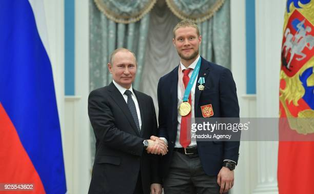 Russia's President Vladimir Putin presents Olympic champion ice hockey player Sergei Andronov with an Order of Friendship at a ceremony to award...