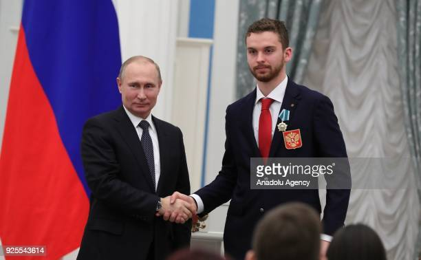 Russia's President Vladimir Putin presents Olympic champion ice hockey goaltender Ilya Sorokin with an Order of Friendship at a ceremony to award...