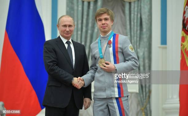 Russia's President Vladimir Putin presents short track speed skater Semyon Yelistratov with an Order for Merit to the Fatherland at a ceremony to...