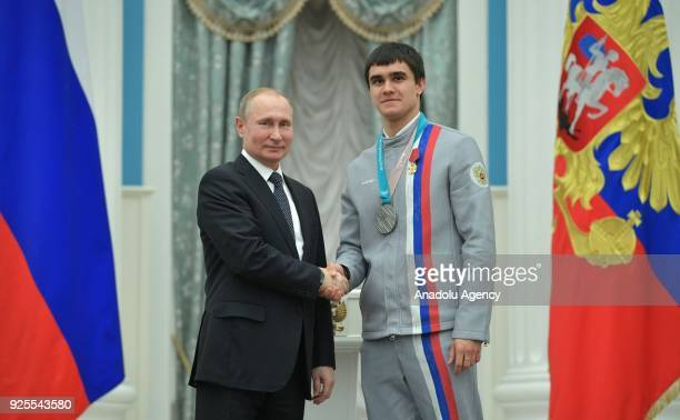 Russia's President Vladimir Putin presents skeleton racer Nikita Tregubov with an Order for Merit to the Fatherland at a ceremony to award Russian...