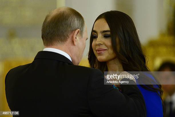 Russias President Vladimir Putin presents the Medal of Pushkin to the vicepresident of the Heydar Aliyev Foundation head of the Foundations...