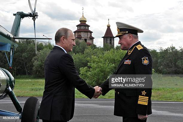 Russia's President Vladimir Putin shake hands with Russian Northern Fleet Commander Admiral Vladimir Korolyov during Navy Day celebrations the in...
