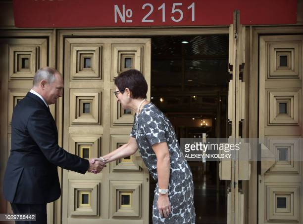 Russia's President Vladimir Putin shakes hands with an unidentified woman at a polling station in Moscow on September 9 2018 during regional...
