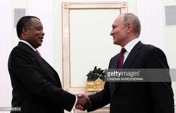 Russia's President Vladimir Putin shakes hands with Congo's President Denis Sassou Nguesso during their meeting at the Kremlin in Moscow on May 23...