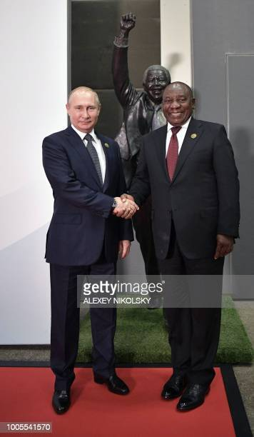 Russia's President Vladimir Putin shakes hands with South Africa's President Cyril Ramaphosa before posing for a group picture during the 10th BRICS...