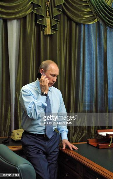 Russia's President Vladimir Putin speaks by phone with farmer Alexander Kuksenko from an office somewhere in the undisclosed location in the Amur...