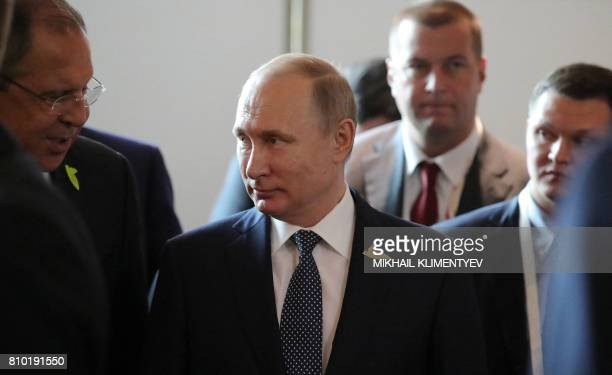 Russia's President Vladimir Putin speaks to Russian Foreign Minister Sergey Lavrov before the G20 summit welcoming ceremony in Hamburg northern...
