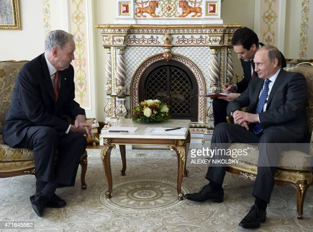 Russia's President Vladimir Putin speaks with Canada's former Prime minister Jean Chretien during their meeting at the NovoOgaryovo residence outside...