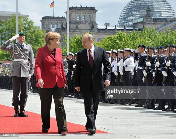 Russia's President Vladimir Putin speaks with German Chancellor Angela Merkel in Berlin on June 1 as they review a guard of honour upon his arrival...