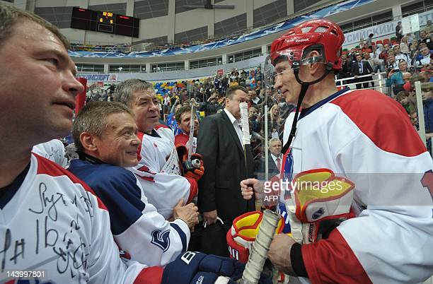 Russia's President Vladimir Putin speaks with his teammates after playing a game at the AllRussian ice hockey festival among amateur teams at...