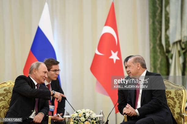 Russia's President Vladimir Putin speaks with his Turkey President Recep Tayyip Erdogan during their meeting in Tehran on September 7 2018 The...