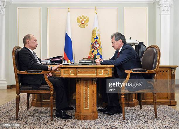 Russia's President Vladimir Putin speaks with newly appointed Defence Minister Sergei Shoigu during their meeting in Putin's NovoOgaryovo residence...