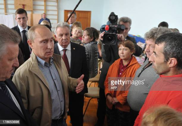 Russia's President Vladimir Putin speaks with people evacuated from the flooded areas of the Russia's Far Eastern Khabarovsk region during their...